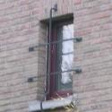Een kleine raam beveiligd met een fijn smeedwerkje.