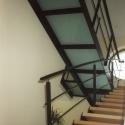 Trap met houten treden en overloop met glaspanelen.