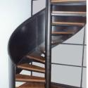 Draaitrap met volle metalen leuning en houten treden.